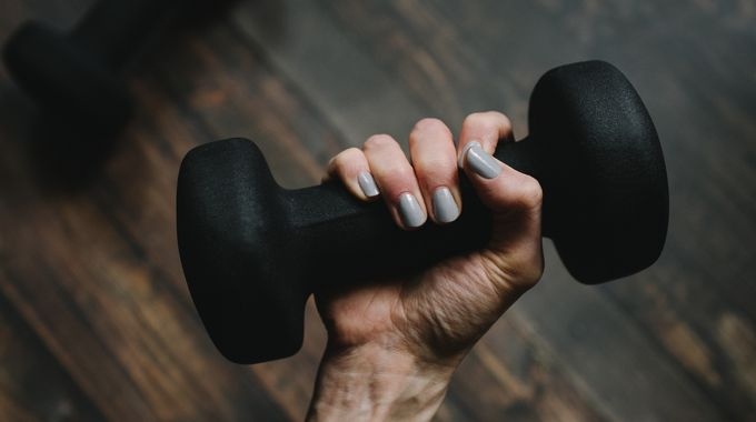 female hand holding weights